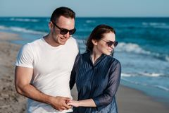 Beautiful young couple on the sandy beach of the sea Stock Photos