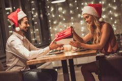 Couple celebrating New Year. Beautiful young couple in Santa hats is looking at each other, holding a gift box and smiling while celebrating New Year in a Royalty Free Stock Photos