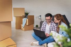 Beautiful young couple shopping on-line using a laptop computer and smiling while sitting in their new apartment after move stock photo