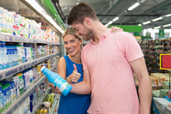 Beautiful Young Couple Shopping Milk In Supermarket Royalty Free Stock Image