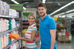 Beautiful Young Couple Shopping Trolley In Supermarket. Beautiful Young Couple Shopping For Trolley In Produce Department Of A Grocery Store - Supermarket Stock Image