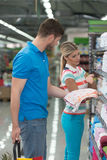 Beautiful Young Couple Shopping Trolley In Supermarket. Beautiful Young Couple Shopping For Trolley In Produce Department Of A Grocery Store - Supermarket Stock Photography