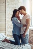 Couple in bedroom. Beautiful young couple is sitting on bed in bedroom. Enjoying spending time together at home Royalty Free Stock Photos