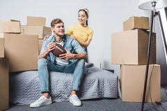 beautiful young couple sitting in bedroom of new home with american