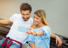 Beautiful young couple sitting on a bench in the city Royalty Free Stock Photo