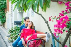 Beautiful young couple sitting on the bench on mediterranean city street with blooming trees. Love, dating, romance, joy and happi. Ness. Lifestyle and tourism Royalty Free Stock Photos