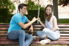 Beautiful young couple sitting on a bench in the park royalty free stock photo