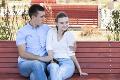 Beautiful young couple sitting on a bench in the park royalty free stock photography