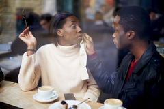 Beautiful young couple sitting in the cafe and the guy tenderly cares for his girlfriend Stock Image