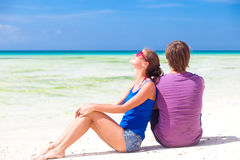 Beautiful young couple sitting and having fun on beach Stock Photos