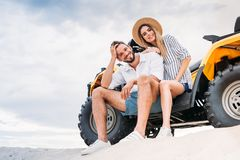 Free Beautiful Young Couple Sitting On ATV On Sandy Dune And Looking Stock Image - 129010511