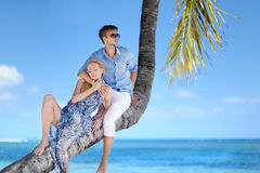 Beautiful young couple sitting on palm tree Stock Photo