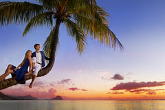 Beautiful young couple sitting on palm tree Stock Photo
