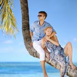 Beautiful young couple sitting on palm tree Royalty Free Stock Image