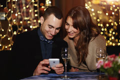 Beautiful young couple sitting in a restaurant and the guy reveals his favorite photos Royalty Free Stock Photography