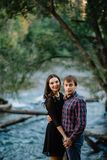 Beautiful young couple sitting on a rock near the river. Family values, love, happiness concept stock photo