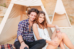 Beautiful young couple sitting in teepee on the beach Royalty Free Stock Photos