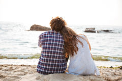 Beautiful young couple sitting together on the beach Royalty Free Stock Image