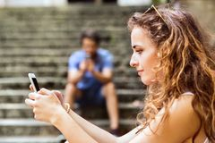 Young couple with smartphones sitting on stairs in town. Beautiful young couple with smart phones sitting on stairs in town, texting. Sunny spring day Royalty Free Stock Image