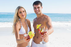 Beautiful young couple smiling at camera holding cocktails Royalty Free Stock Images