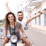Couple riding motor scooter in old city street. Beautiful young couple is smiling while riding a scooter Stock Photography