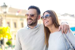 Beautiful young couple smiling while walking outdoors. On sunny day Royalty Free Stock Image