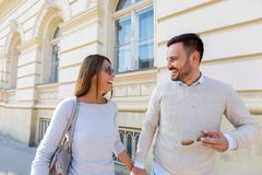 Beautiful young couple smiling while walking outdoors. On sunny day Royalty Free Stock Photography