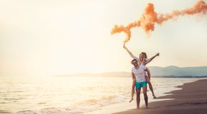Beautiful young couple with smoke bomb on the beach. Beautiful young couple with smoke bomb in hand is standing outdoors at golden summer background Royalty Free Stock Photos
