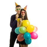 Beautiful young couple stand in front of the camera holding a lot of balloons with the requisites and smiling Stock Photography