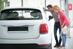 Beautiful young couple standing at the car dealership and making Royalty Free Stock Images
