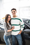 Beautiful young couple standing at the car dealership and making their decision Royalty Free Stock Photo