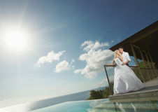 Beautiful young couple standing close to pool before wedding. Royalty Free Stock Images
