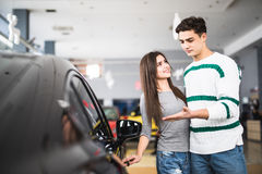 Beautiful young couple standing at the dealership choosing the car to buy Stock Images