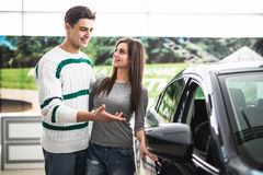 Beautiful young couple standing at the dealership choosing the car to buy. Man pointed on car. Royalty Free Stock Image