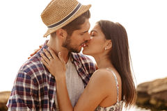 Beautiful young couple standing and kissing on the beach Stock Photos