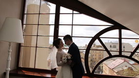 Beautiful young couple standing near the window stock footage