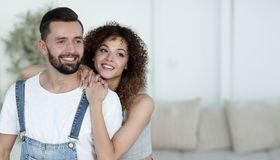 Beautiful young couple standing in a new apartment. Photo has a copy of space stock photo