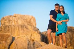 Beautiful young couple standing on the rocks at sunset stock photography