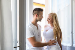 Beautiful young couple standing at the window Stock Images