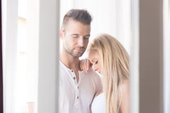 Beautiful young couple standing at the window Stock Image