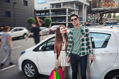 Beautiful young couple stands near a car, makes a shopping stock photo