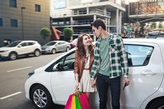 Beautiful young couple stands near a car, makes a shopping royalty free stock images