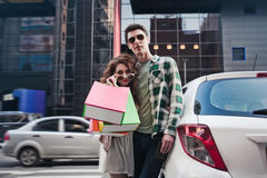 Beautiful young couple stands near a car, makes a shopping royalty free stock photography