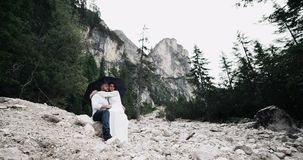 Beautiful young couple stay on the rock under the umbrella hugs each other ,background amazing landscape. Beautiful young couple stay on the rock under the stock footage