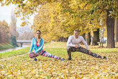 Beautiful young couple stretching together and preparing for run. In the park. Autumn environment Royalty Free Stock Photo