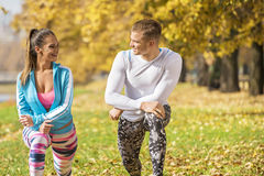 Beautiful young couple stretching together and preparing for run in the park. Autumn environment Stock Image