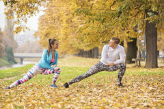 Beautiful young couple stretching together and preparing for run. In the park. Autumn environment Royalty Free Stock Photos