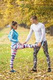 Beautiful young couple stretching together and preparing for run. In the park. Autumn environment Royalty Free Stock Photography