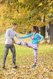 Beautiful young couple stretching together and preparing for run. In the park. Autumn environment Stock Photo