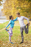Beautiful young couple stretching together and preparing for run. In the park. Autumn environment Stock Image